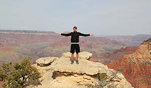 A happy tourist at a viewpoint in South Grand Canyon.
